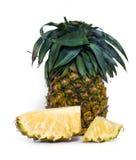 Fruta fresca de la piña con los pedazos cortados aislados en blanco Fotografía de archivo