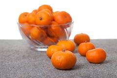 Fruta fresca de las clementinas con el bol de vidrio foto de archivo