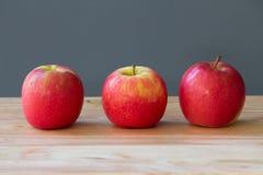 Fruta fresca de tres manzanas en la tabla Fotografía de archivo libre de regalías