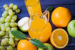 Fruta fresca y jugo del multifruit en el jarro en todavía de la tabla la vida de madera Fotos de archivo