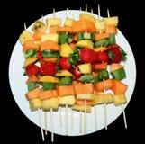 Fruta Kebabs en la placa blanca imagenes de archivo