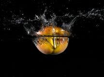 Fruta lanzada en agua Foto de archivo libre de regalías