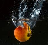 Fruta lanzada en agua Imagenes de archivo