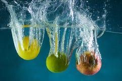 Fruta lanzada en agua Foto de archivo