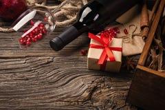 Fruta madura de la granada con una copa de vino, una botella y un regalo en un fondo de madera imágenes de archivo libres de regalías