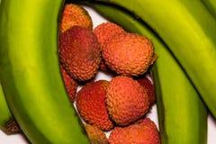 Fruta orgánica fresca del lichi y plátanos verdes imagen de archivo