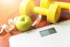 Fruta, pesa de gimnasia y escala, quemadura gorda y pérdida de peso foto de archivo