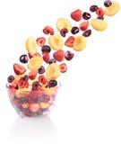 Fruta que cae en un bol de vidrio. Fotos de archivo