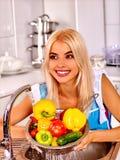 Fruta que se lava de la mujer en la cocina Foto de archivo libre de regalías