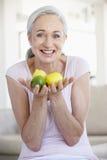 Fruta sênior da terra arrendada da mulher Imagem de Stock