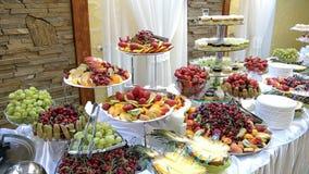 Fruta sabrosa - peras de los melocotones de la piña del kiwi de las fresas de la cereza en la tabla de comida fría almacen de video