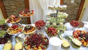 Fruta sabrosa - peras de los melocotones de la piña del kiwi de las fresas de la cereza en la tabla de comida fría metrajes