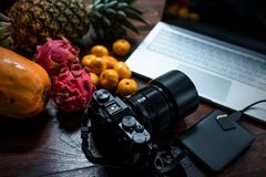 Fruta tropical cerca del ordenador portátil moderno en fondo de madera Forma de vida del vegano imagen de archivo libre de regalías