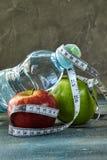 Fruta, una botella de agua, un metro en un azul con un fondo del divorcio fotografía de archivo