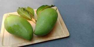 Fruta verde cruda del mango en la placa de madera imagen de archivo