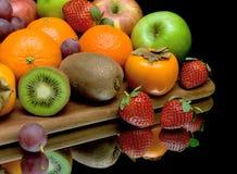 Fruta y bayas en un fondo negro con el primer de la reflexión Imagen de archivo libre de regalías
