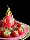 Fruta y fresas del dragón en negro Fotos de archivo