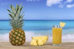Fruta y jugo de la piña en verano en la playa Fotografía de archivo libre de regalías