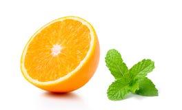Fruta y menta a medias anaranjadas en el fondo blanco imagen de archivo libre de regalías