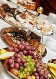 Fruta y pasteles en la tabla de banquete Fotos de archivo