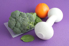 Fruta y verdura con el equipo del ejercicio Imagen de archivo libre de regalías