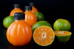 Fruta y zumo de naranja anaranjados verdes Fotos de archivo libres de regalías