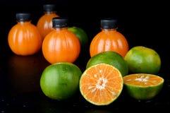 Fruta y zumo de naranja anaranjados verdes Foto de archivo libre de regalías