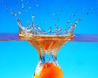 Frutas anaranjadas con salpicar el agua Foto de archivo libre de regalías