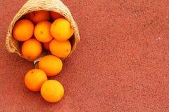 Frutas anaranjadas en cesta de mimbre Foto de archivo libre de regalías