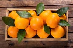 Frutas anaranjadas frescas con las hojas en una caja de madera Imagen de archivo