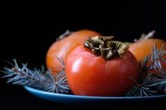 Frutas anaranjadas maduras del caqui y las ramas de árbol en un cuenco azul en un fondo negro imágenes de archivo libres de regalías