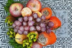 Frutas asperjadas con el azúcar en polvo en una placa en un fondo azul Imágenes de archivo libres de regalías