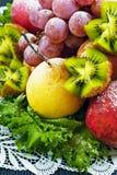 Frutas asperjadas con el azúcar en polvo en una placa en un fondo azul Foto de archivo libre de regalías