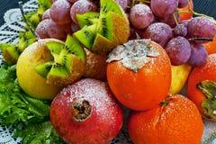 Frutas asperjadas con el azúcar en polvo en una placa en un fondo azul Imagen de archivo libre de regalías