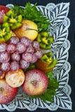 Frutas asperjadas con el azúcar en polvo en una placa en un fondo azul Fotos de archivo libres de regalías
