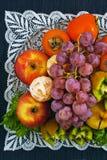 Frutas asperjadas en una placa en un fondo azul Fotografía de archivo libre de regalías
