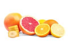 Frutas cítricas coloridas en un fondo blanco Corte el pomelo y las naranjas Rebanadas nutritivas del plátano Frutas por completo  Foto de archivo libre de regalías