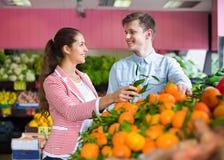 Frutas cítricas de compra morenas hermosas de la muchacha y del novio Imágenes de archivo libres de regalías
