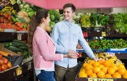 Frutas cítricas de compra morenas jovenes de la muchacha y del novio i Foto de archivo