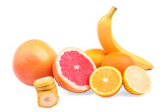 Frutas cítricas enteras y cortadas aisladas en un fondo blanco Plátano nutritivo y pomelos jugosos Naranjas y limones frescos del Foto de archivo