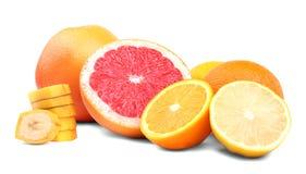Frutas cítricas maduras aisladas en un fondo blanco brillante Pomelos y limones amargos Pedazos nutritivos del plátano Vitamina C Foto de archivo libre de regalías