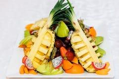 Frutas clasificadas en una placa blanca en una tabla de comida fría en un partido Imágenes de archivo libres de regalías
