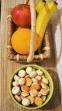 Frutas coloridas en la cesta y las galletas Imagen de archivo libre de regalías