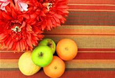 Frutas coloridas en la tabla con las flores y el mantel rojos Fotos de archivo