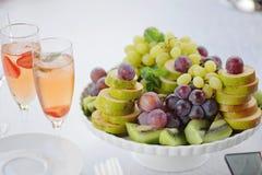 Frutas coloridas frescas incluyendo el primer blanco del cuenco de la pera del kiwi de las uvas Imagenes de archivo
