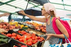 Frutas de compra de la mujer en el mercado verde Foto de archivo