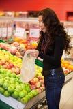 Frutas de compra de la mujer joven Fotos de archivo libres de regalías