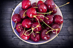 Frutas de la cereza en florero azul Foto de archivo