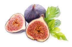 Frutas de la higuera enteras y de la parte con las hojas Foto de archivo