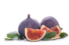 Frutas de la higuera enteras y de la parte con las hojas Imagen de archivo libre de regalías